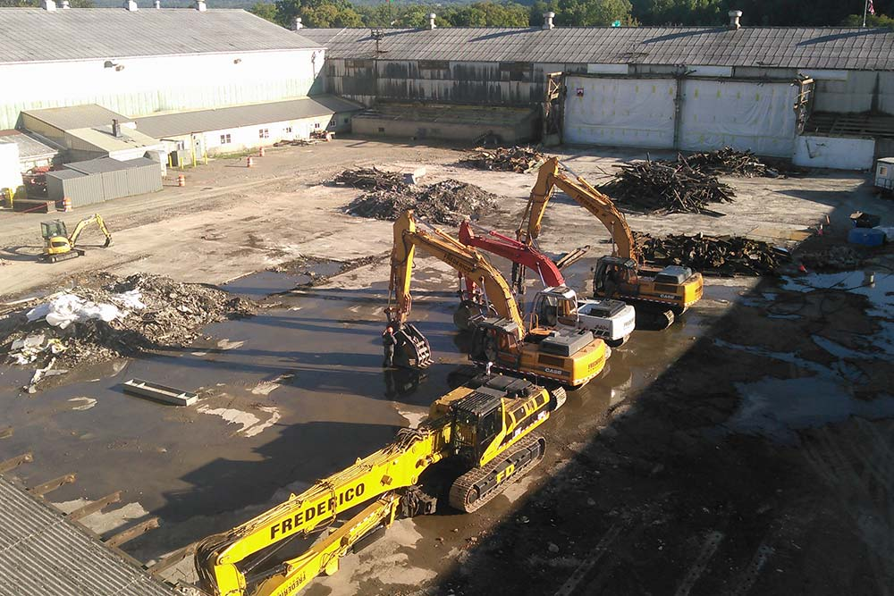 cranes cleaning up a demolished building